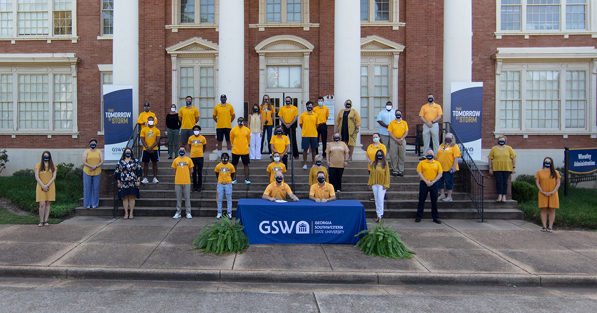 mayor signs proclamation surrounded by GSW supporters wearing gold