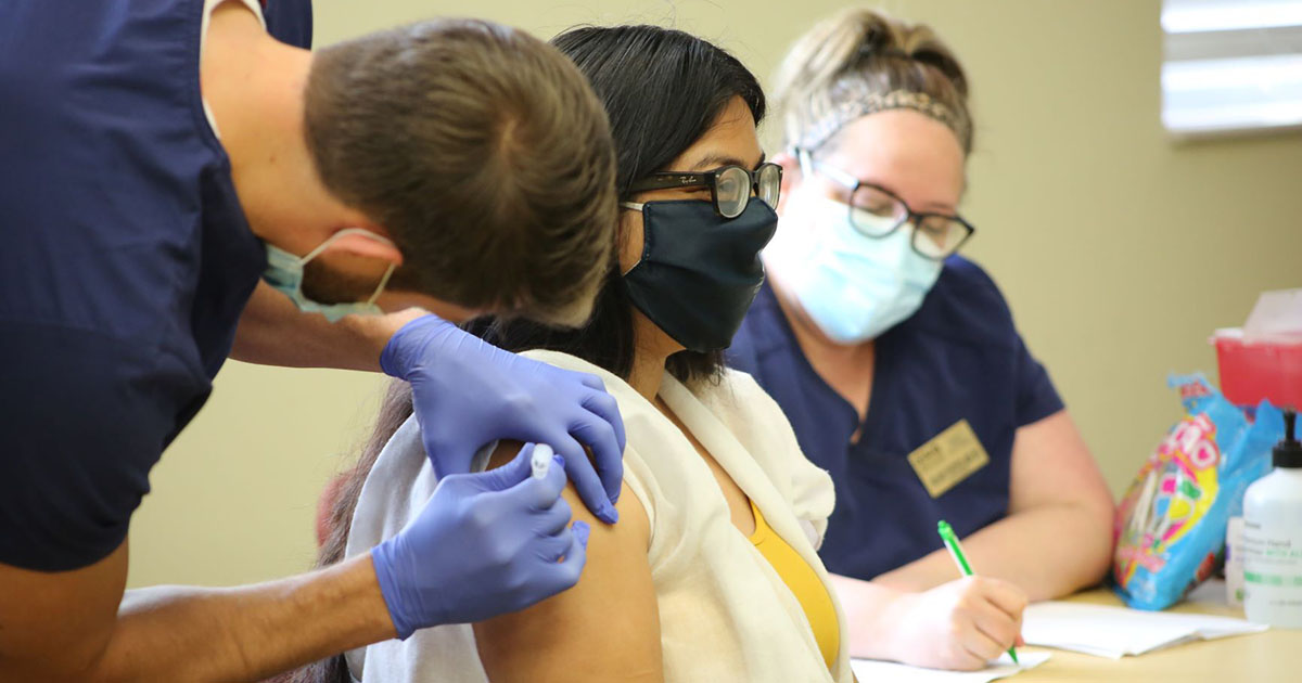 Staff member receives vaccine from nursing student