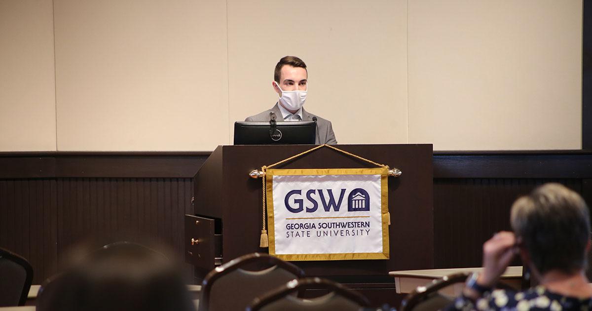 Caleb Kot gives presentation at symposium